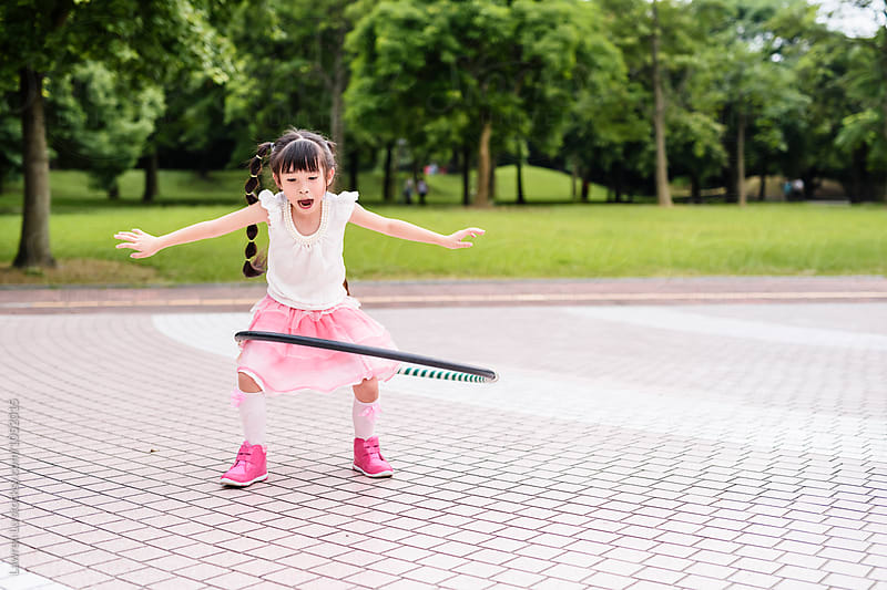 Girl twisting hulahoop in park by Lawren Lu for Stocksy United