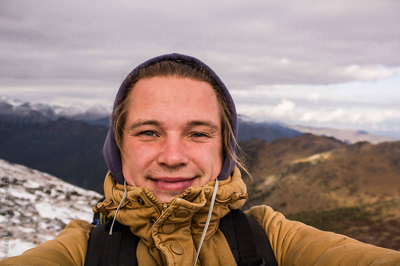 Selfie of young backpacker against of mountains by Danil Nevsky for Stocksy United