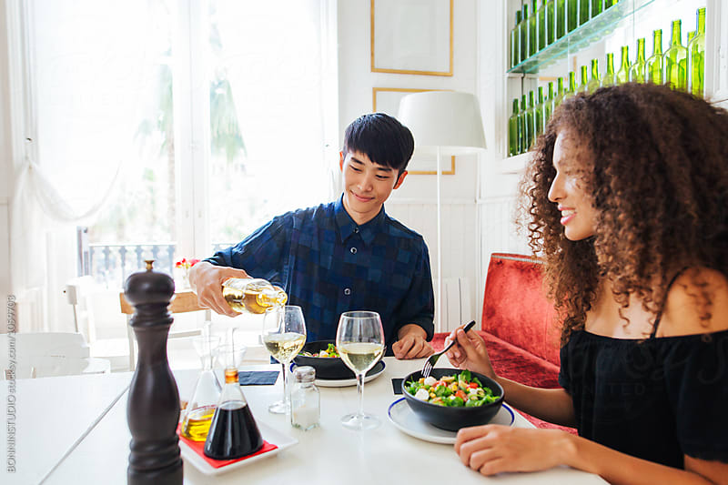 Multi-ethnic couple eating in a cool restaurant.  by BONNINSTUDIO for Stocksy United