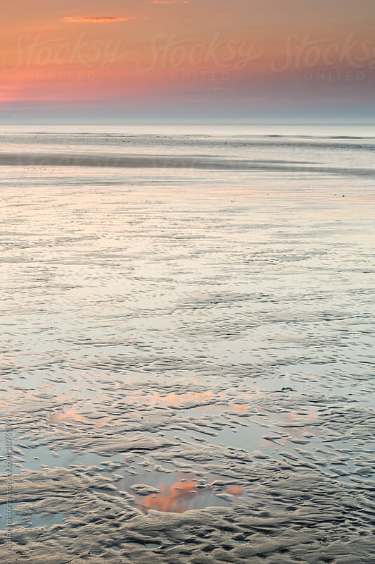 Reflections of sunset on a beach at low tide by Marilar Irastorza for Stocksy United