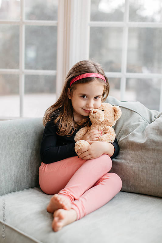 Beautiful young girl sitting on a big chair with her teddy bear by Jakob for Stocksy United