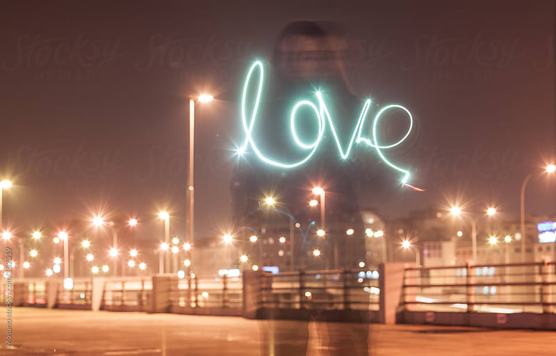 Woman Writing Word Love With Light by Mosuno for Stocksy United