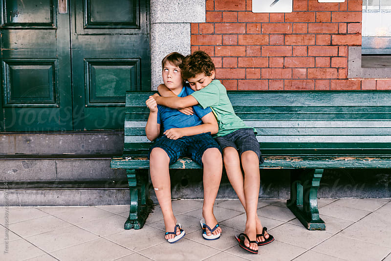 One boy hugging other while annoyed sitting on bench by Trent Lanz for Stocksy United