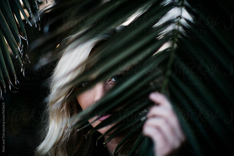 Blonde girl peeking from behind a palm tree by Matt and Tish for Stocksy United