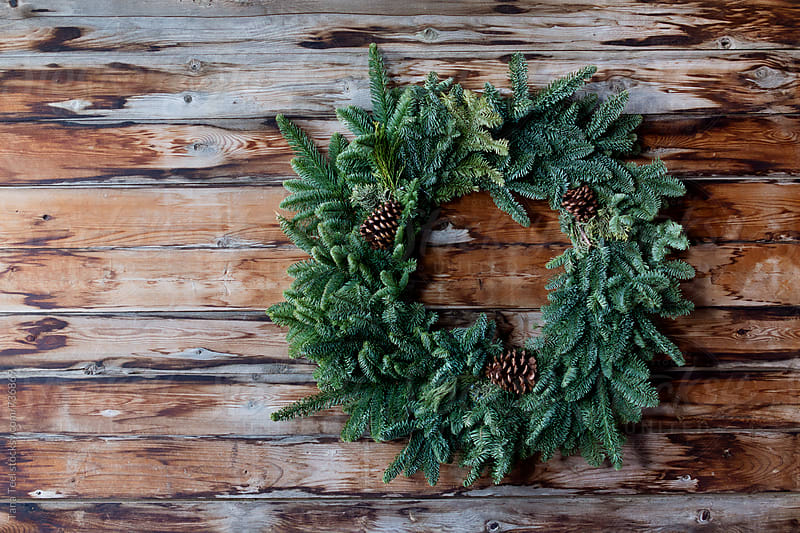 Simple evergreen wreath hangs on rustic wall  by Tana Teel for Stocksy United