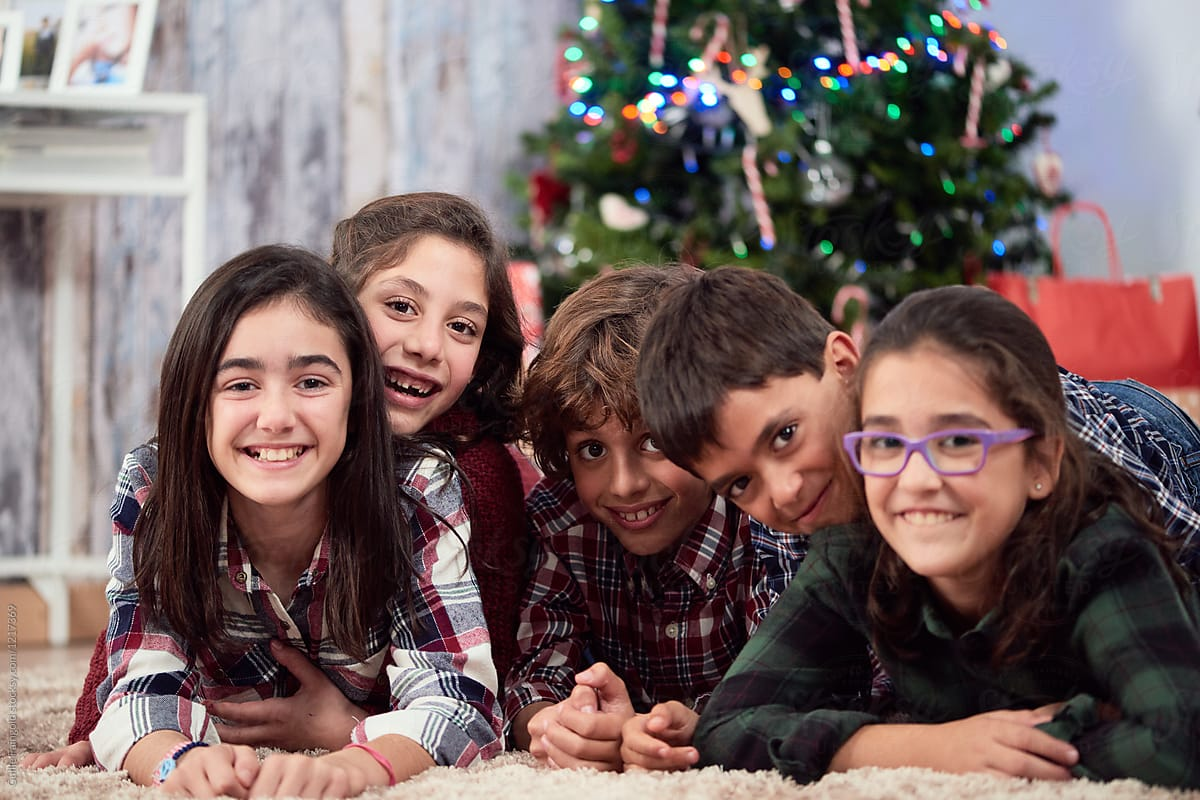 Happy kids smiling at camera under Christmas tree. by Guille Faingold for  Stocksy United b3d14c123