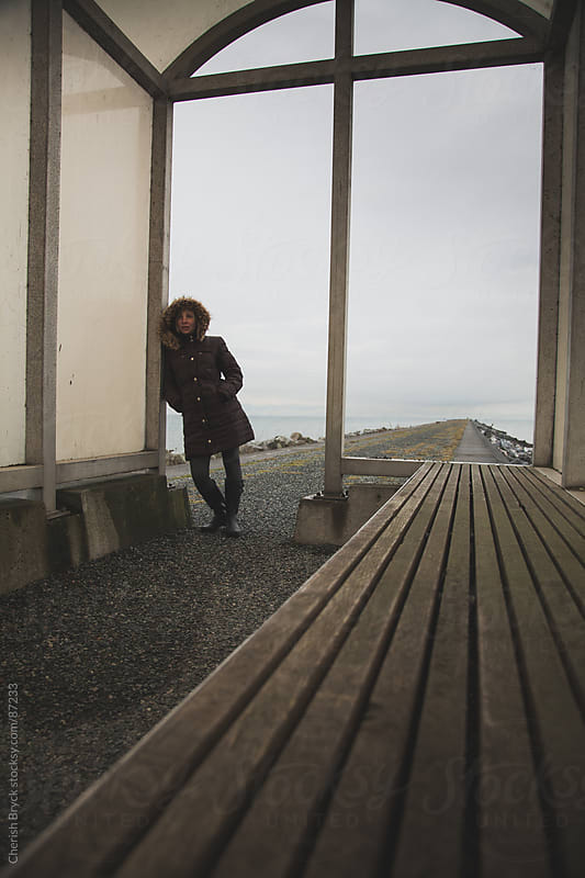 Woman leans against building with the ocean behind her. by Cherish Bryck for Stocksy United