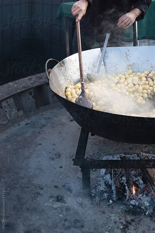 Cooking potatoes at the market by Jill Chen for Stocksy United