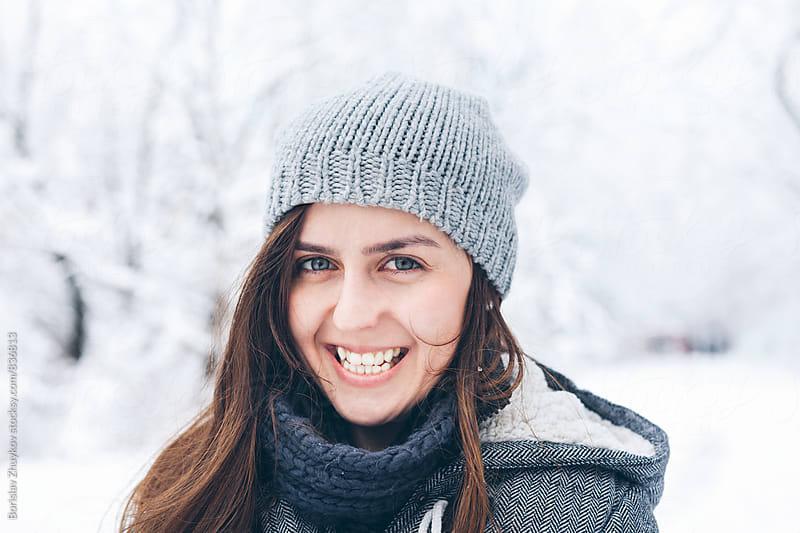 Portrait of happy woman wearing knit hat in snowy field by Borislav Zhuykov for Stocksy United