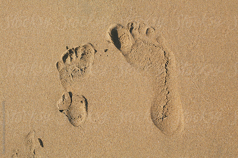 Two  different size foot prints by Dejan Ristovski for Stocksy United