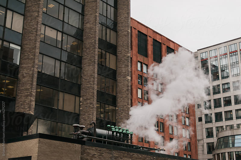 Steam Rising from a Rooftop in front of Large City Buildings by Briana Morrison for Stocksy United