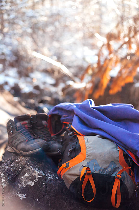 Backpack, jacket, and shoes on the rock. Hiking gear. by Dimitrije Tanaskovic for Stocksy United