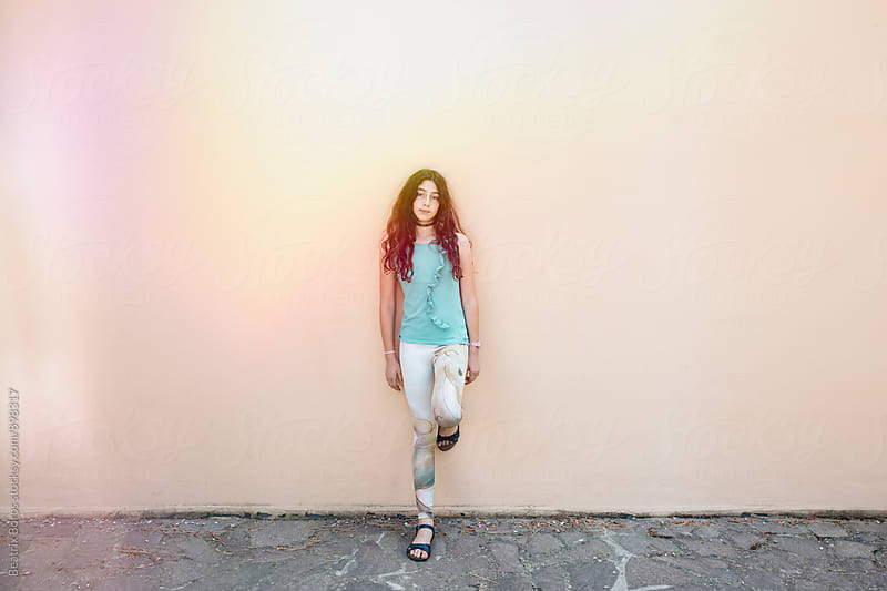 Pre-teenager girl standing in front of a wall by Beatrix Boros for Stocksy United