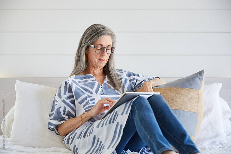 Senior woman with grey hair online with digital tablet by Trinette Reed for Stocksy United