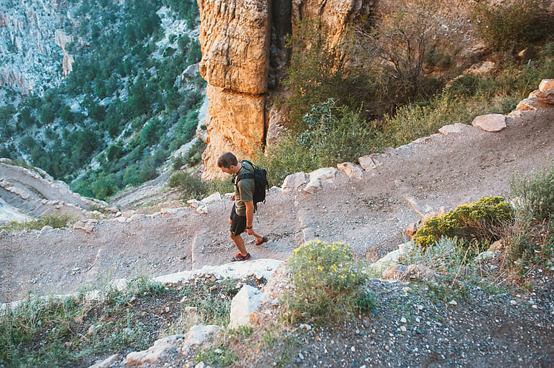 Man Hiking into Grand Canyon by michelle edmonds for Stocksy United