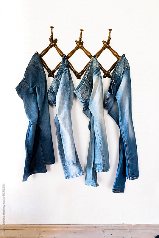 Pair of jeans suspended on wall hanger by Pixel Stories for Stocksy United