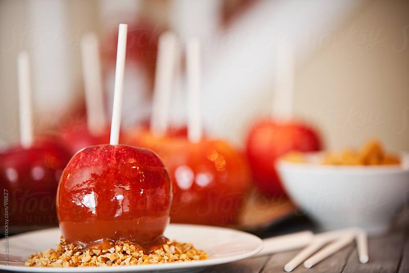 Apples: Caramel Apple Sitting in Nuts by Sean Locke for Stocksy United