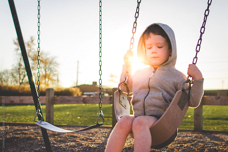 Little boy on a swing by Lindsay Crandall for Stocksy United