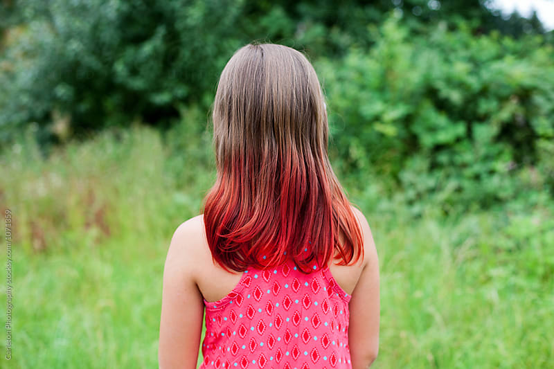 Girl with red tipped hair stands in front of green plants by Carleton Photography for Stocksy United