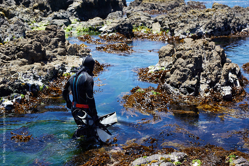 Diver with flippers walking in rocky water by Martí Sans for Stocksy United