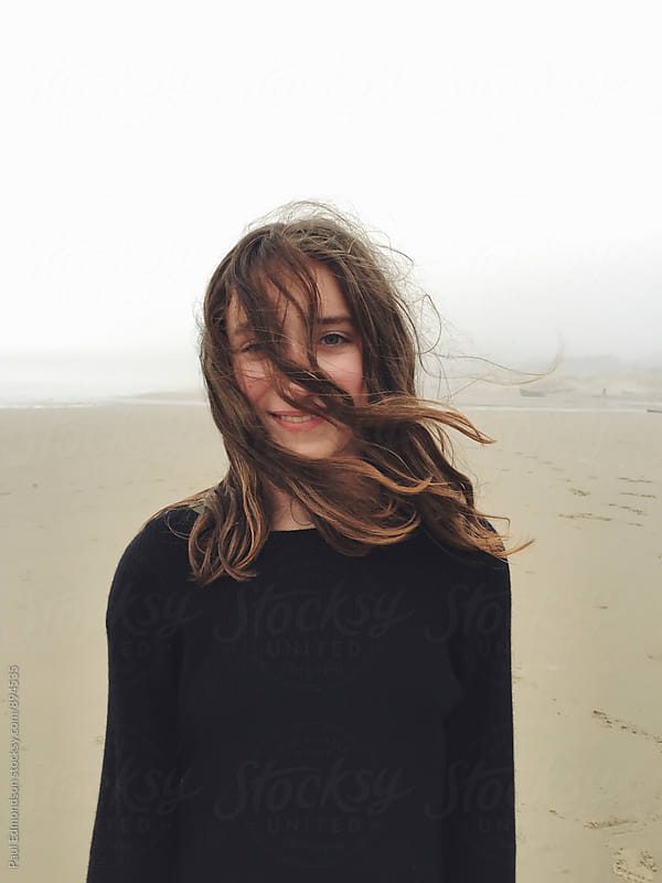 Portrait of smiling twelve year old girl on beach, hair blowing across face by Paul Edmondson for Stocksy United