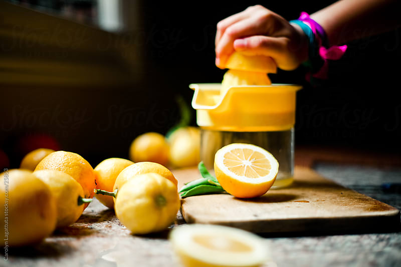 Young girl squeezing lemons for homemade lemonade by Carolyn Lagattuta for Stocksy United