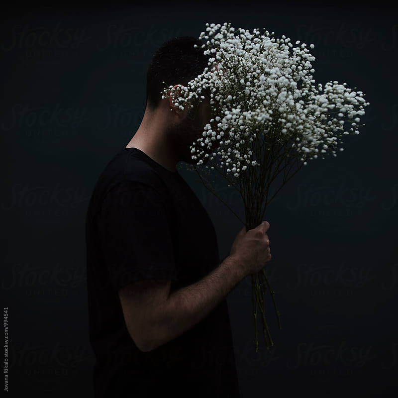 Man is hiding behind a flowers by Jovana Rikalo for Stocksy United