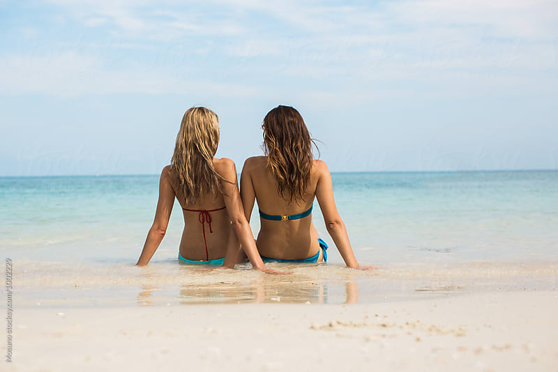 Two Girlfriends Sitting at the Beach by Mosuno for Stocksy United