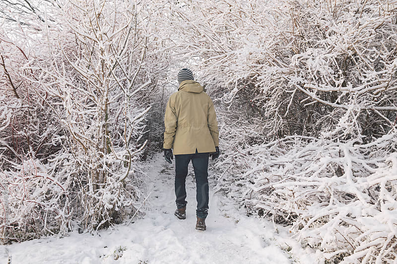 Man walking on snow covered path by Lior + Lone for Stocksy United