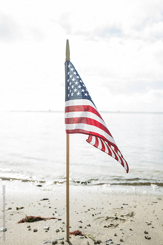 United States Flag Along the Shore by suzanne clements for Stocksy United