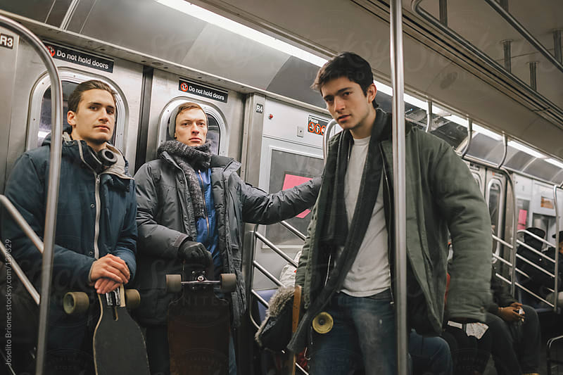 Young Men Friends Riding the Train of New York Subway by Joselito Briones for Stocksy United