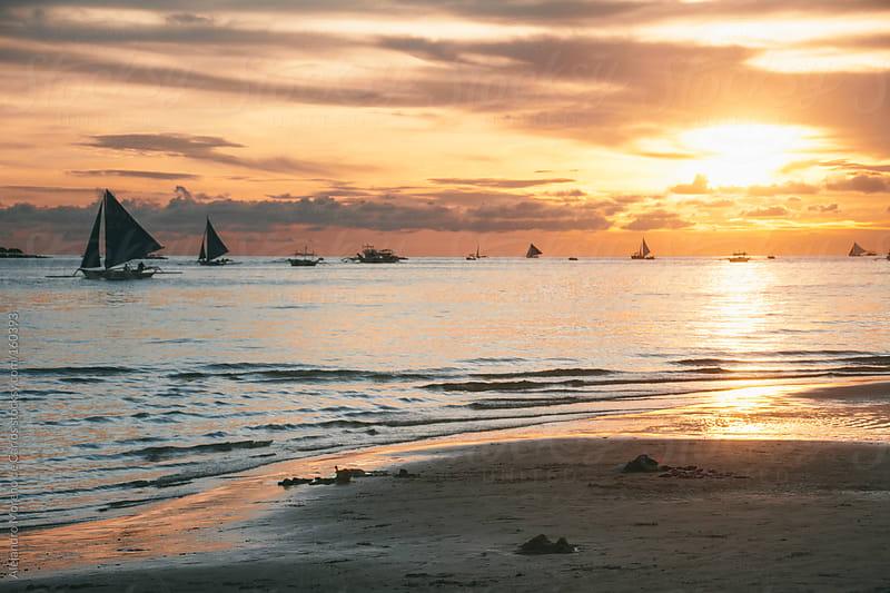 Sailboats on a beach at sunset by Alejandro Moreno de Carlos for Stocksy United