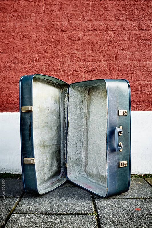 A empty suitcase on the pavement by James Ross for Stocksy United