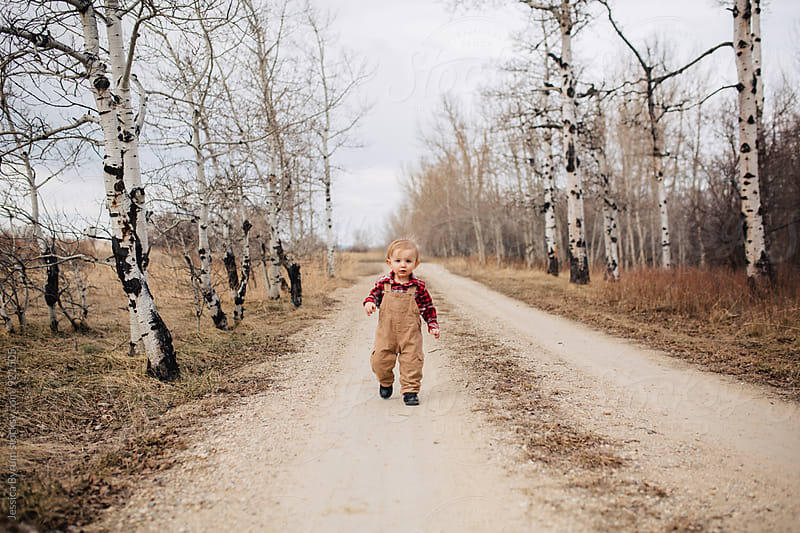 Toddler boy walking down road in bib overalls by Jessica Byrum for Stocksy United