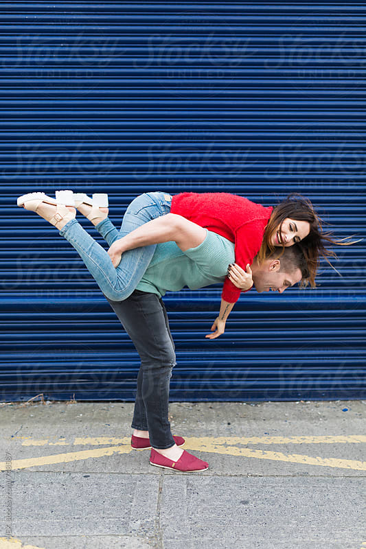 Young Couple Together Against a Blue Shutter by HEX. for Stocksy United