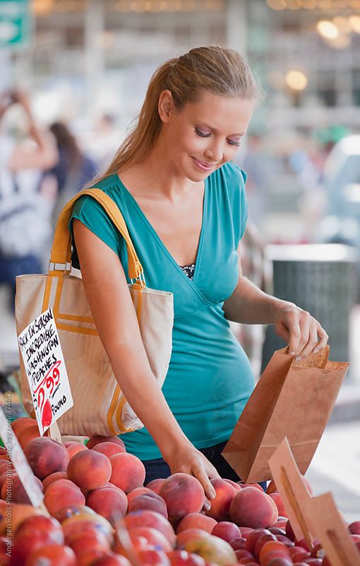 Smiling woman shopping for peaches on farmer's market by Andersen Ross Photography for Stocksy United
