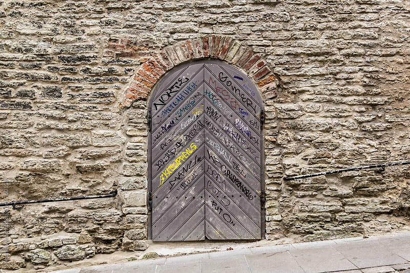 Historic door with contemporary graffiti/scribblings  by Melanie Kintz for Stocksy United