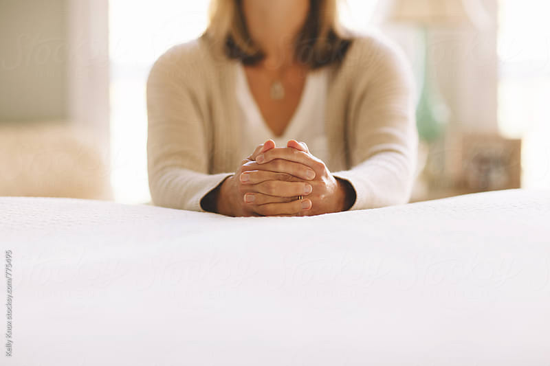 woman praying next to a bed by Kelly Knox for Stocksy United