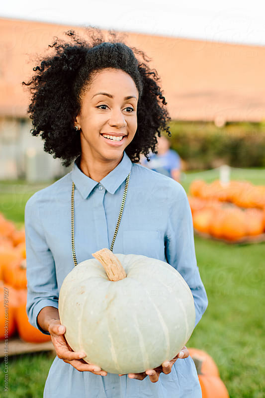 Woman holding a big off white pumpkin by Kristen Curette Hines for Stocksy United