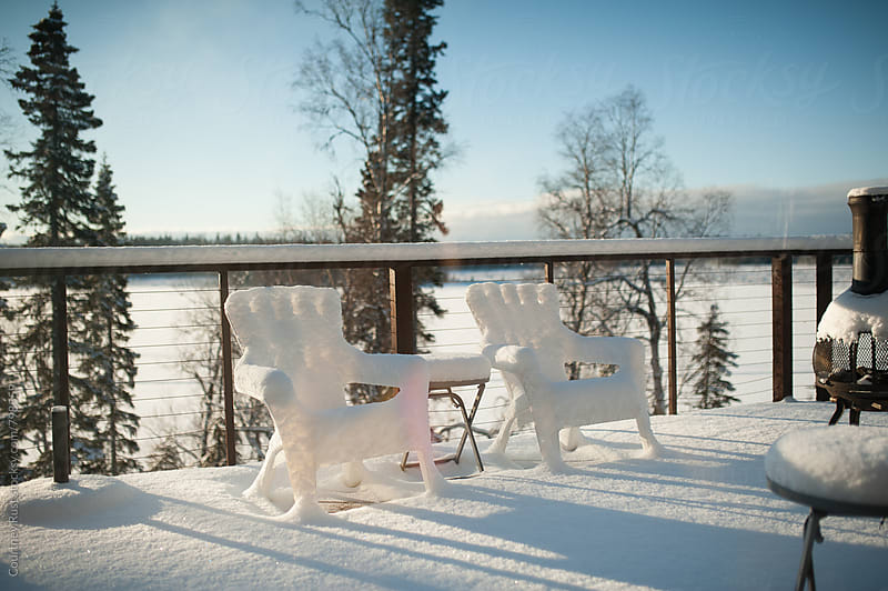 Snow covered chairs on wooden deck by Courtney Rust for Stocksy United