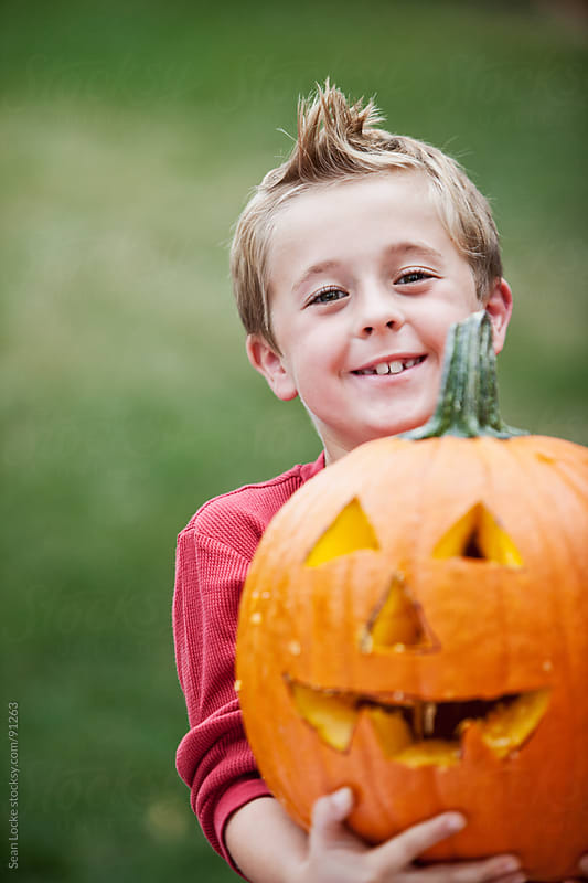 Pumpkins: Laughing Boy Carrying Jack-O-Lantern by Sean Locke for Stocksy United