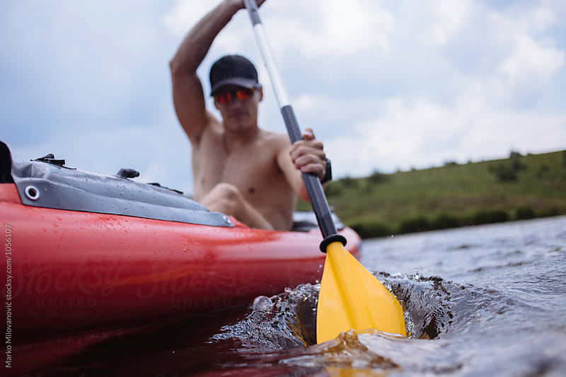 Man kayaking on lake by Marko Milovanović for Stocksy United