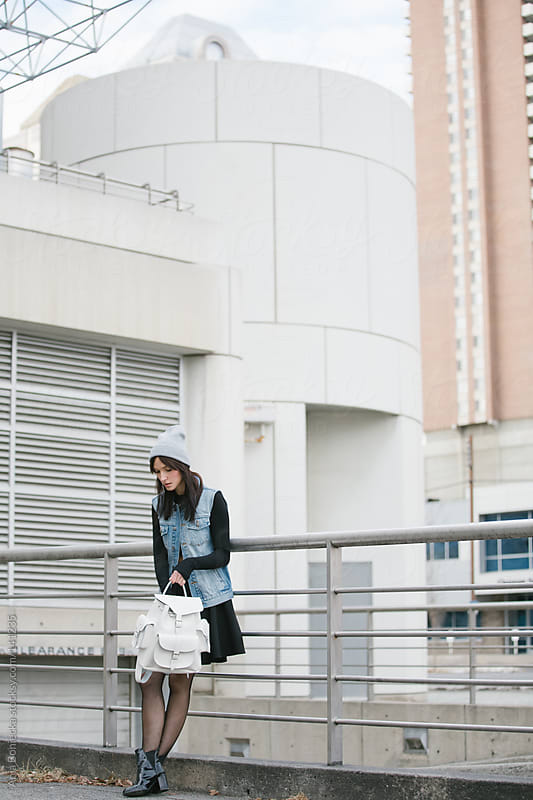 A trendy young student loping down into her backpack by Ania Boniecka for Stocksy United