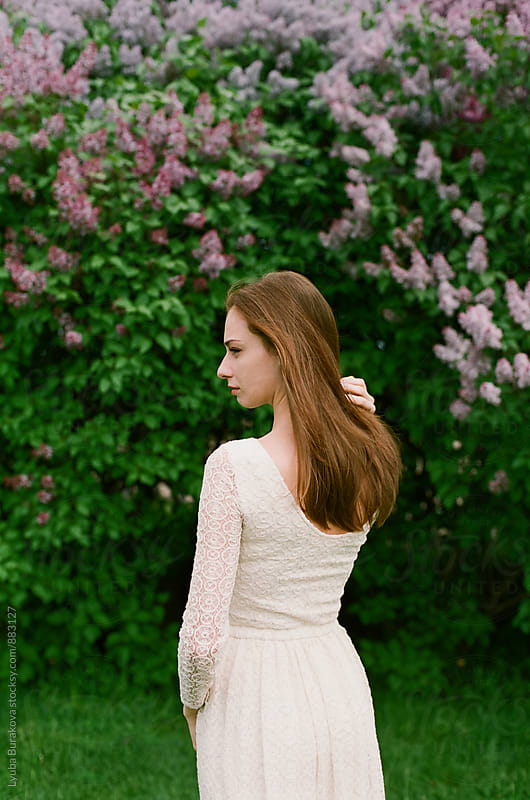 Woman posing among lilac by Lyuba Burakova for Stocksy United