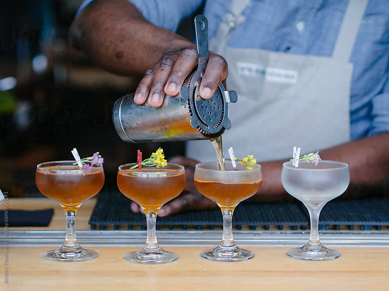 Man wearing apron pouring cocktails at bar  by Jeremy Pawlowski for Stocksy United