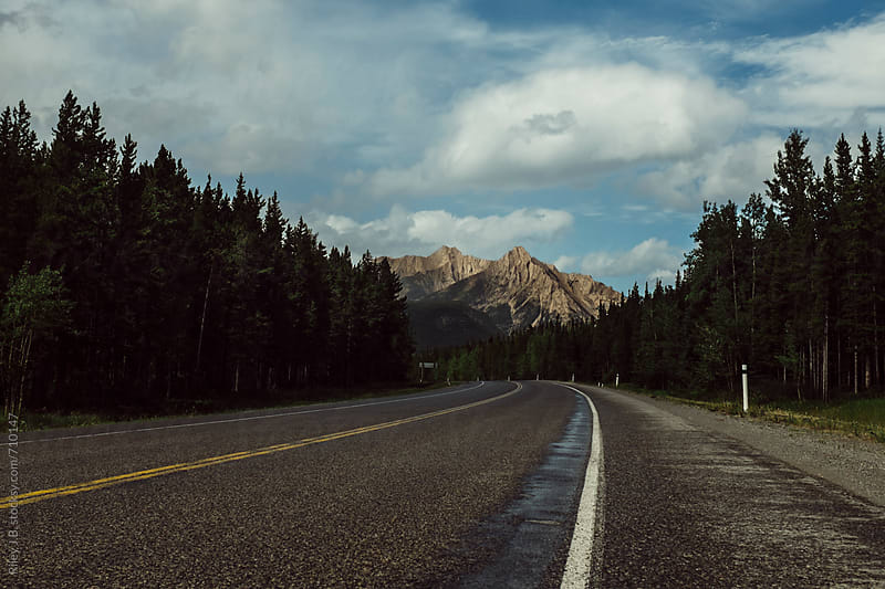Empty highway leading to mountain by Riley Joseph for Stocksy United