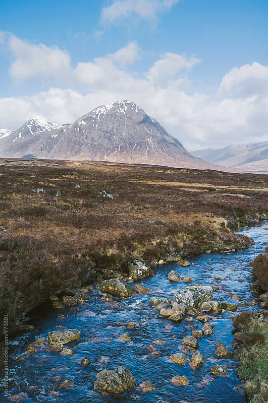 A stream in the Scottish Highlands with a mountain in the background by Ivo de Bruijn for Stocksy United