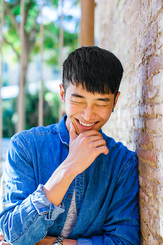 South Korean young man laughing in the street. by BONNINSTUDIO for Stocksy United