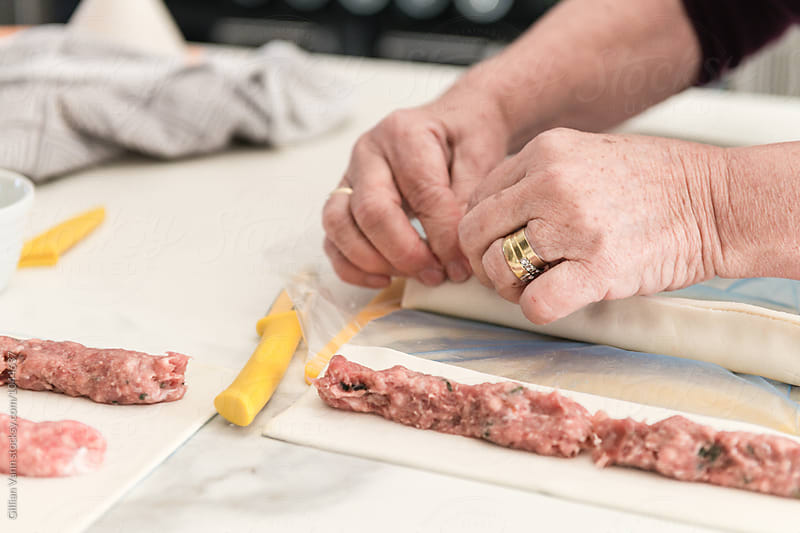 making sausage rolls at home by Gillian Vann for Stocksy United