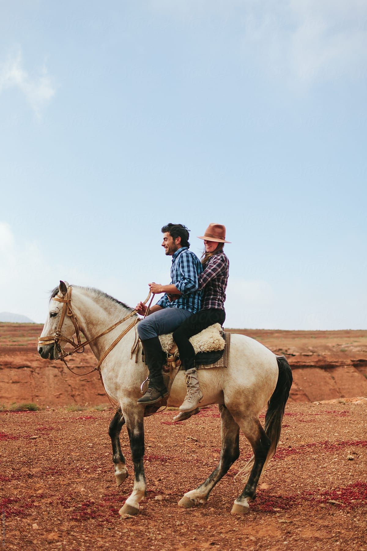 Young Couple Riding A White Horse In The Desert By Mattia Stocksy United